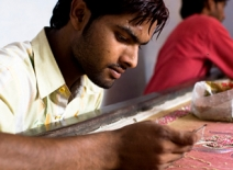 Male homeworker, hand-embelishing fabric, India